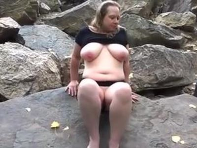 Chubby mature plays on the rocks