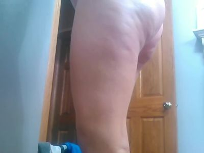 Blonde pregnant wife rubbing on lotion after shower