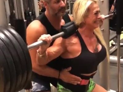 mature bodybuilder woman grunts like a beast under heavy barbell